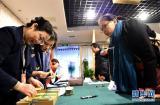 3月1日,两会新闻中心外国记者组的工作人员(左)在发放记者证。 当日,设在北京梅地亚中心的2016年全国两会新闻中心开始发放外国记者证、外国驻华使馆新闻官旁听证等。 新华社记者 刘军喜 摄